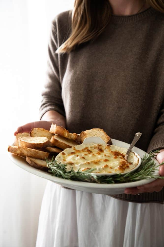 platter of cheesy artichoke dip with bread