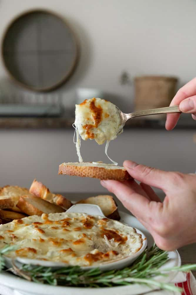 platter of cheesy artichoke dip on bread