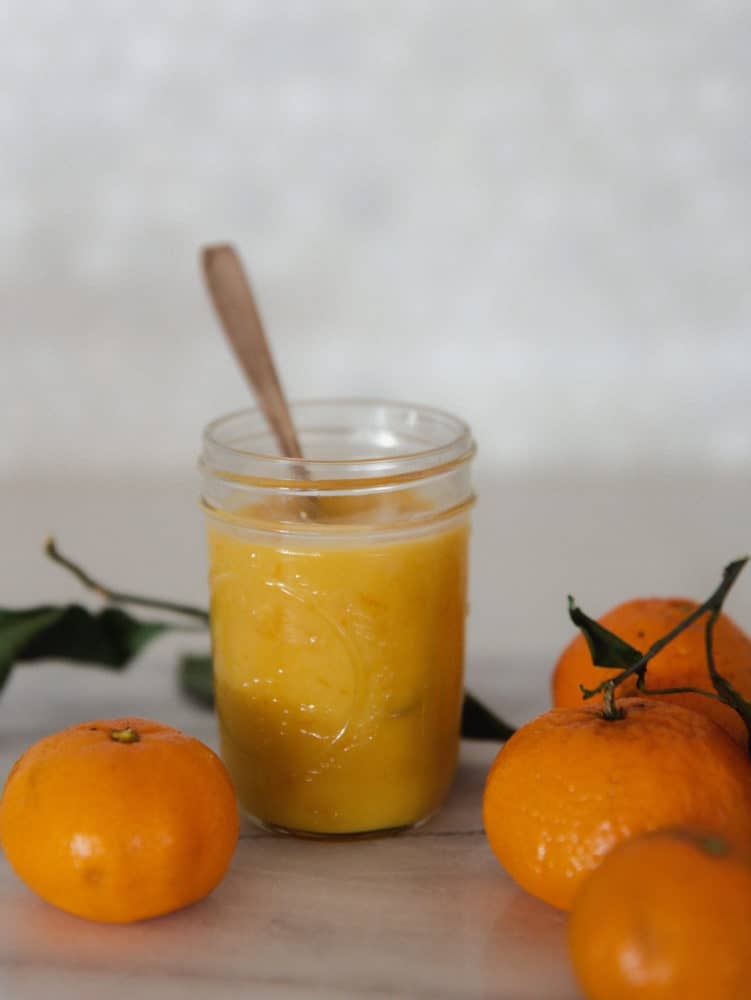 Jar of orange curd on countertop with mandarin oranges.