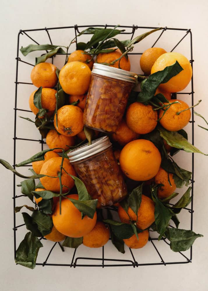 Basket of oranges with jars of orange marmalade sitting on top.