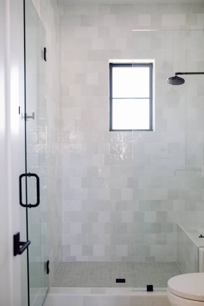 Shower with white Cloe tile and black hardware with grey accents.