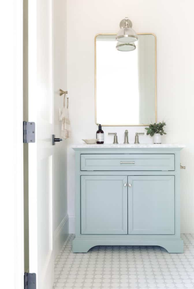 Beautiful small bathroom design with blue vanity and white walls with mixed metals.