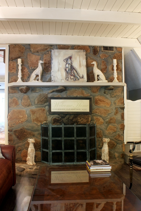 stone fireplace with dog figurines and painting