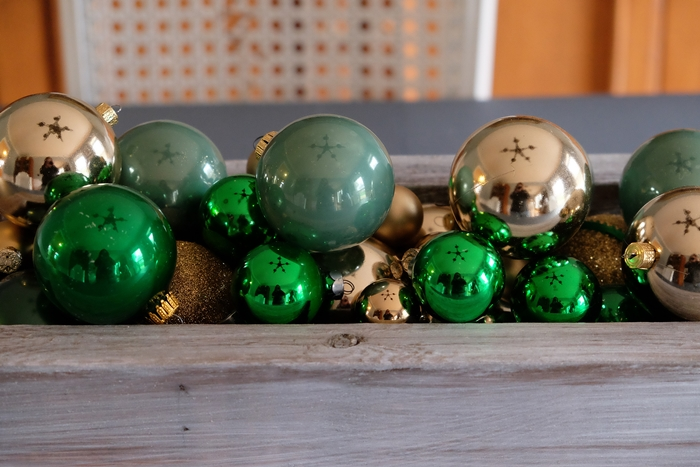 green ornaments in wooden box