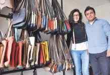 Carolina Báez y Fabián Arizmendi muestran los bolsos hechos con tejidos ancestrales y cuero que serán exhibidos en la pasarela de la moda.
