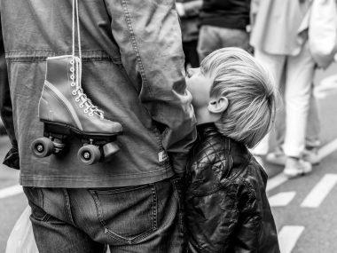 Sohn schaut Vater an mit Rollschuh über der Schulter