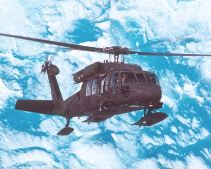 UH-60L Black Hawk, equipped with skis, flies over Alaskan glacier