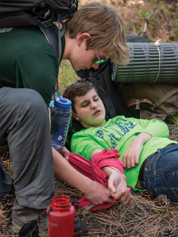 """Tending to a """"victim"""" during a wilderness first-aid challenge."""
