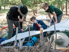 Scouts work on a shelter using sticks and plastic they collected.