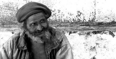 Seorang lelaki tua berjanggut sedang tersenyum.