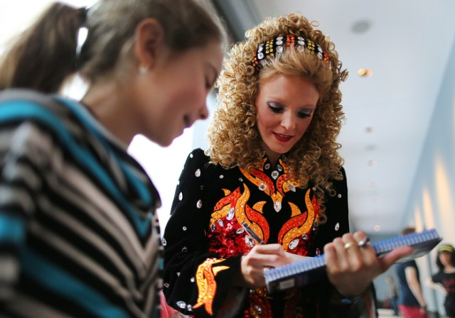 Boston-3/29/13- The reining world champion Irish Dancer Claire Greaney(rt) autographs a program for Maggie Fleming, 9 from Islip, NY at The World Irish Dancing Championships being held at the Hynes Convention Center.  It is only the second time in it's 40 year history that the eight-day event is held outside Ireland and Scotland. Organizers expect twenty-thousand people from around the globe to attend the event.
