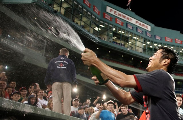 Sep 20, 2013; Boston, MA, USA; Boston Red Sox relief pitcher Koji Uehara (19) of Japan sprays champagne on the fans after they clinched the AL East with a win over the Toronto Blue Jays at Fenway Park.