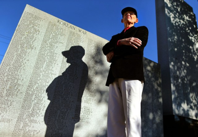 Mansfield-10/25/13-- Earl Austin is a Korean War vet and wrote a book about Mansfield servicemen who died in wartime. He stands at the town war memorial.