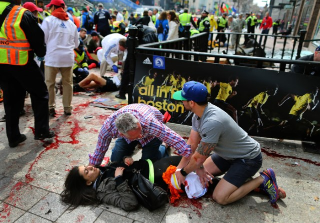 Boston-0415/13 Sydney Corcoran from Lowell is helped by Matt Smith (left) from Boston and Zack Mione from Portland Oregon on the sidewalk at the site of the first Boston Marathon bombing. They saved her life by using t-shirts around her legs and applied pressure to stop the bleeding. A piece of shrapnel from the pressure-cooker bomb the size of a cell phone severe her femoral artery. Her mother Celeste lost both legs.