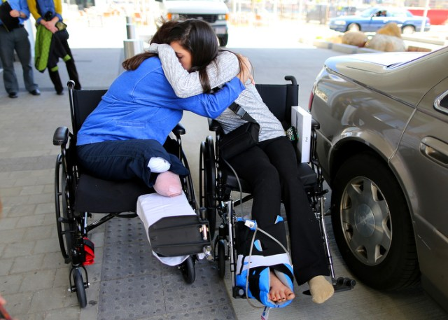 """Boston-5/03/13- Boston Marathon bombing survivors Celeste Corcoran from Lowell and her daughter Sydney hug at Spaulding Rehab Hospital as Sydney was discharged. Celeste lost both her legs and Sydney almost died after a massive leg injury tore her femoral artery. Sydney's departure both comforts and unsettles Celeste.""""if Sydney would of died, I think I would of died with her."""" Celeste said."""