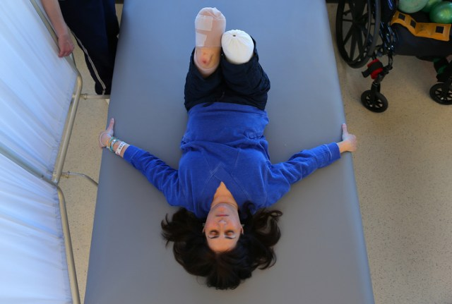 """Boston-5/03/13-Celeste Corcoran worked hard in physical therapy doing leg lifts at Spaulding Rehab Hospital. She had to wait for her legs to heal before getting fitted for prosthetics. She was determined at this point to return to """"the new normal"""" as she called it."""