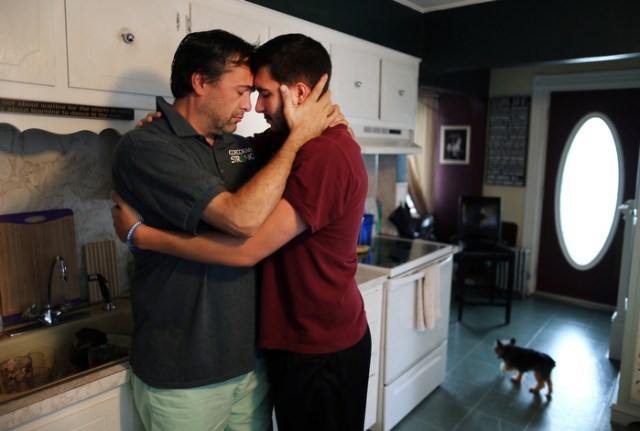 """Lowell--08/3013 Kevin Corcoran breaks down into tears in the kitchen of his home as he embraces his son Tyler after having an emotional day at work. Kevin's wife, Celeste lost both legs in the 1st Boston Marathon bombing, and his daughter Sydney was seriously injured. Kevin saved Celeste's  life by using his belt and another one to stop the bleeding in her legs after the bombing. He admits that he should go to ptsd counseling but says he gets  the most support from his family. """"I don't have nightmares. I'm dealing with it."""" he said."""