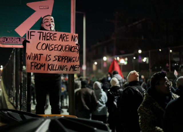 Boston. Dec. 4, 2014. A protestor wears a Guy Fawkes mask as protestors march on Boston streets on Thursday night.