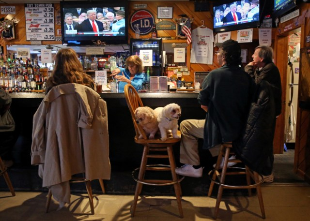 """Scott """"Dusty"""" Dunton was accompanied by his dogs, Sissy and Buck-A-Boo while watching President Donald Trump take the oath of office on television at the Toy Town Pub in Winchendon, MA on  January 20, 2017. Dunton said he voted for trump because, """"I was afraid Hillary would put us into debt. We need a stronger mind in there, I think he can save us."""" The town of Winchendon voted for President Obama in 2012, but this election more people backed the Republican candidate and voted for Trump."""