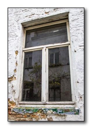 Een oud raam met mosgroene vensterbank