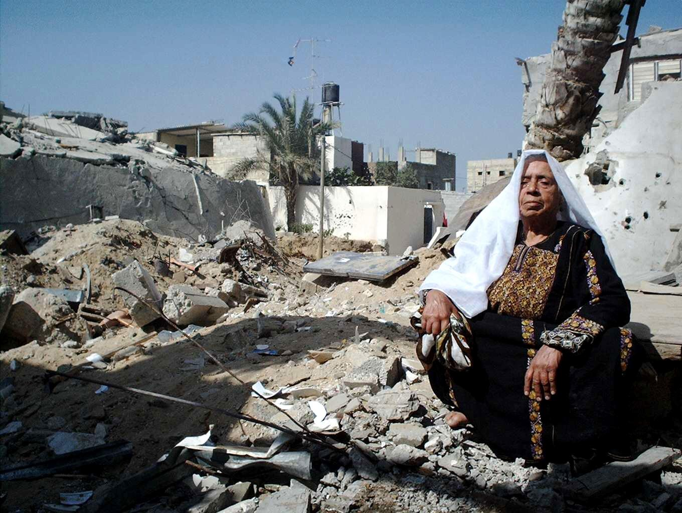 A Palestianian woman in Gaza, next to rubble created by the Israeli military, for her sitting pleasure, I assume.