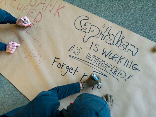 "Photo by Bradley. November 30, 2011. A vacant bank owned by Wells Fargo is occupied in Santa Cruz. An occupier writes ""Capitalism Is Working As Intended!"" on a banner."