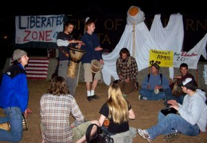 "A nice drum circle took place in front of the sign that normally says, ""Univetisty of California, Santa Cruz."" A banner hung over the sign reading, ""Liberated Zone."""