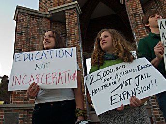 Demonstrators hold signs at the Clock Tower in downtown Santa Cruz to protest jail expansion.