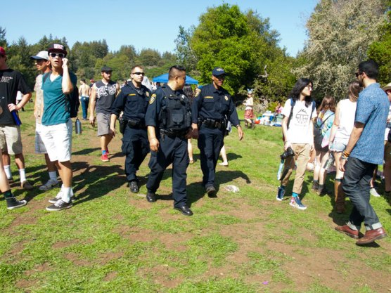 University of California Police walk past 420 attendees in UCSC's Porter Meadow