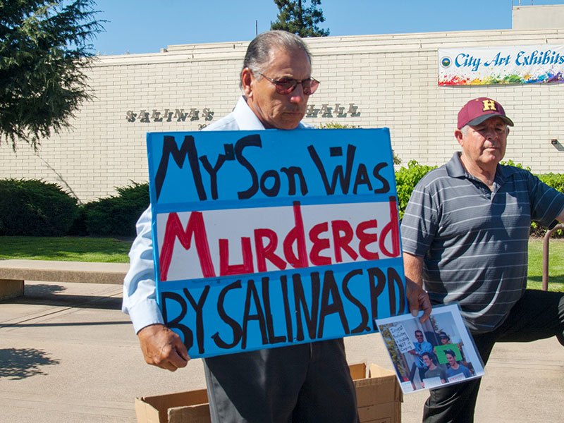 """Frank Alvarado Sr. holds a sign on October 1, 2014 in front of Salinas City Hall reading, """"My Son Was Murdered By Salinas PD."""" Frank Alvarado Sr. is also displaying a photo of his son, Frank Alvarado, who is holding a sign on May 14, 2014 stating """"Invest in Protecting and Healing, Not in Caging"""" before speaking at a Sin Barras rally at the Santa Cruz Courthouse for building strong communities in California, not more jails!"""