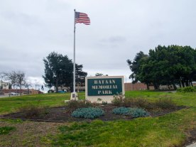Bataan Memorial Park, a triangular park on an incline situated between Market Street, Main Street, and Monterey Street in the middle of Salinas, was created to honor the 105 Salinas and Pajaro Valley military members who fought in the Philippines during World War II. The sign pictured was made by Ty Brooks of Sunset Customs, metal design solutions of Salinas, and installed in October 2012 as part of the Bataan Memorial Park Revitalization Project.