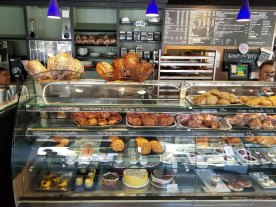 Fresh baked breads are displayed, along with croissants, scones, turnovers, sticky buns, cinnamon rolls, cookies, cakes, and other desserts, at Heather's Patisserie.