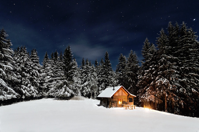 A log cabin in the snowy woods, lit up by a fire and candles is definitely hygge.
