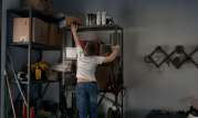 A young boy reaches for an unsecured gun on a high shelf in a garage
