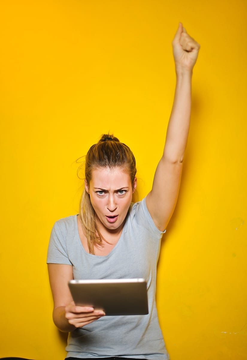 woman raises arm in victory while holding a tablet