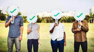 Four people stand in a park near a city skyline holding signs with checkmarks over their faces.