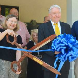 Dr. Peter Liggett and his wife Jean Collins use giant ceremonial scissors to cute the ribbon at their practice.