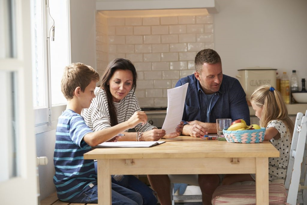 Parents-Helping-Children-With-Homework-At-Kitchen-Table-638922898_2125x1416-1024×683