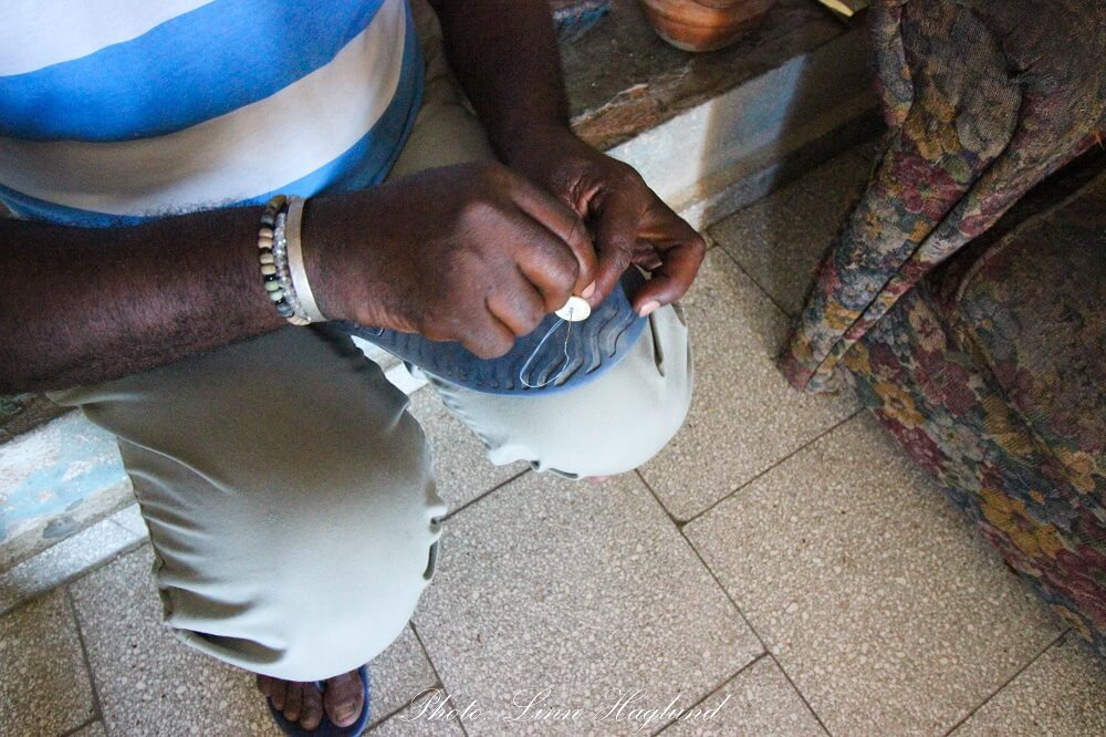 Anas uncle is sewing a button to the bottom of his broken flip flop