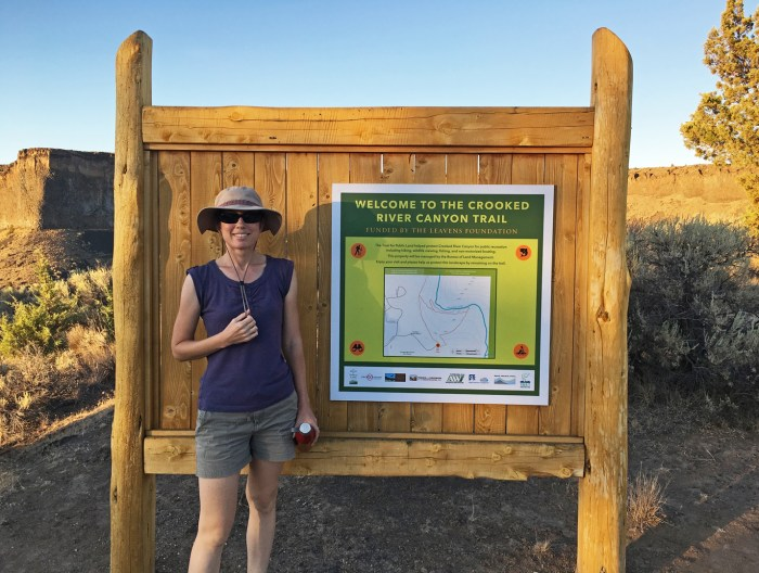 Christina standing next to the sign for the Crooked River Canyon Trailhead