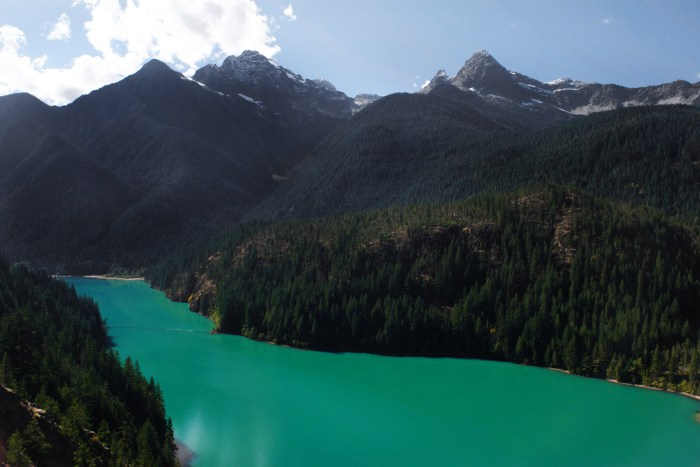 Sea-foam green lake waters of Diablo Lake surrounded by snow-capped peaks of the Cascades