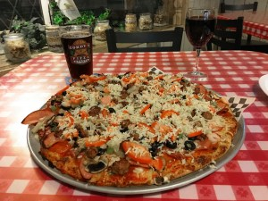 Extravaganza pizza on a red and white checkered tablecloth with a glass of beer and glass of red wine at Gordy's