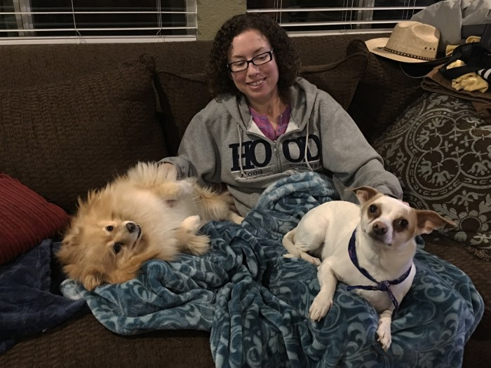 Christina on the couch at Michael's sister's house with their jack russell and pomeranian on her lap