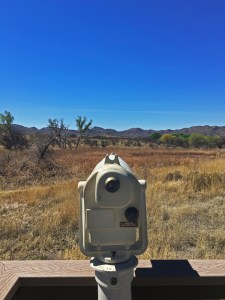 Scope on the boardwalk with wetland and grassland landscape in the background