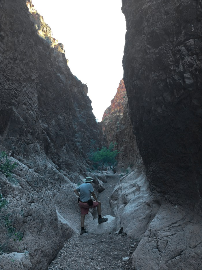 My father with his foot up on a boulder in the middle of the narrowing trail of Closed Canyon