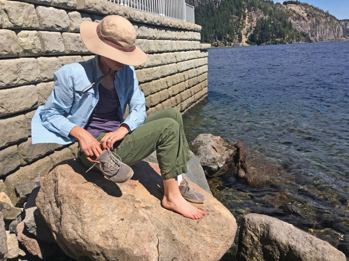 Sitting on a rock at Crater Lake, removing my Lems shoes, socks, and toe spacers