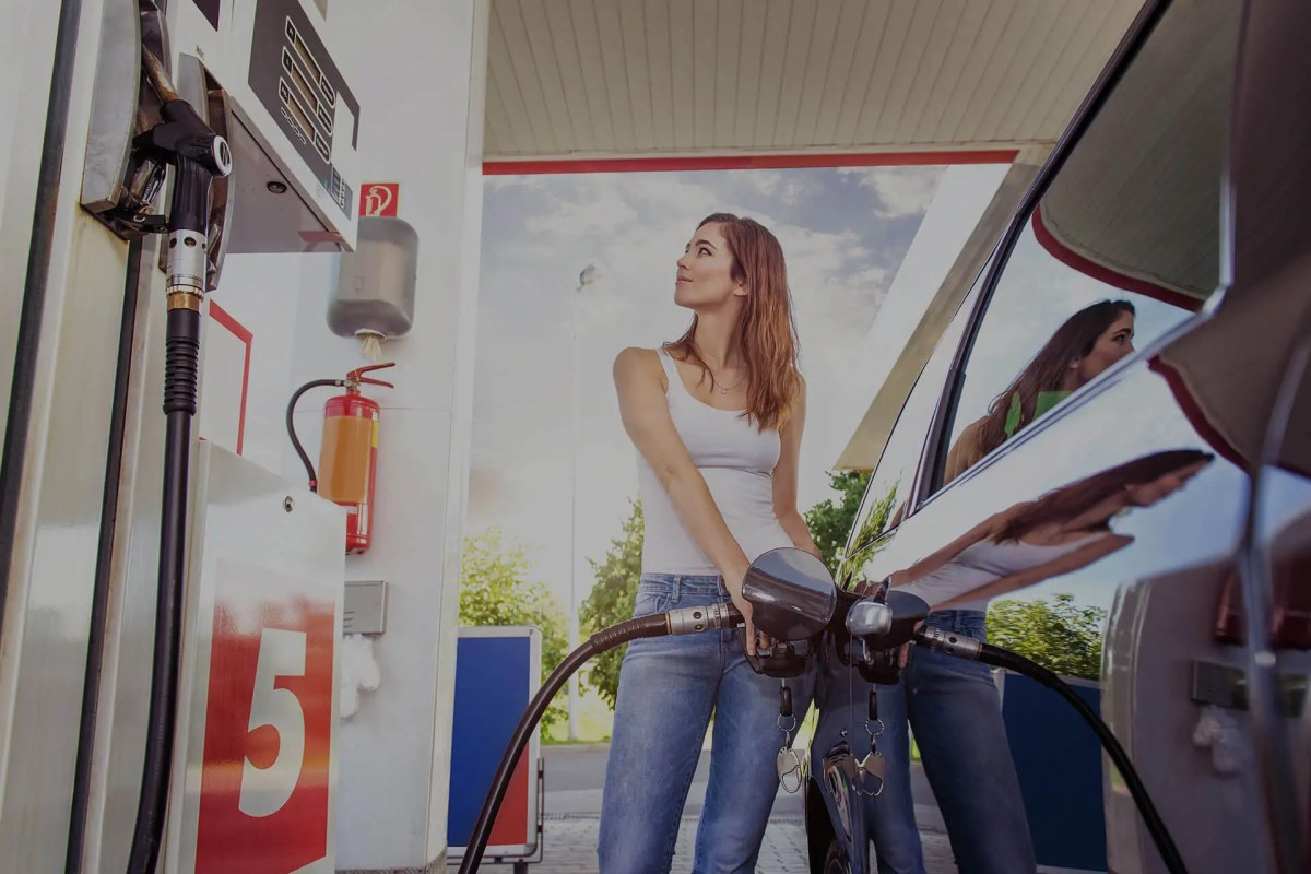 Woman pumping gas at gas station