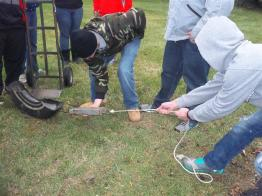 student pulling tire across grass