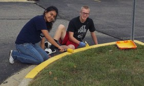 Students painting a curb yellow