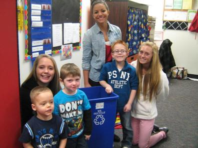 Students posing with recycling bin